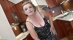 Granny with a shaved slit tries pleasing herself in the kitchen